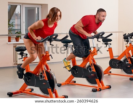 Happy couple doing indoor biking in a fitness club