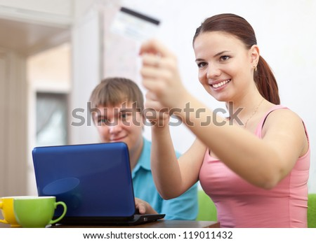 happy couple doing shopping in internet with credit card at home