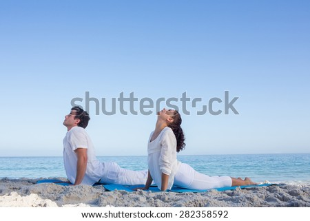 Happy couple doing yoga beside the water at the beach - stock photo