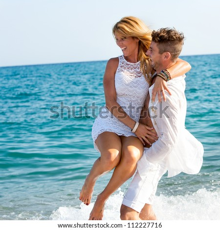 Happy couple dressed in white playing in waves.