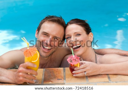 Happy couple drinking cocktails - stock photo