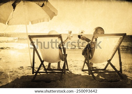 Happy couple drinking cocktails while relaxing on their deck chairs against grey background - stock photo