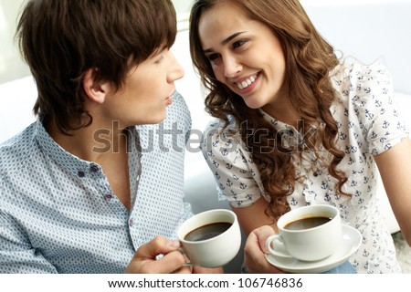 Happy couple drinking coffee and looking at each other with affection - stock photo