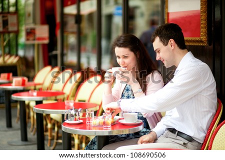 Happy couple drinking coffee in a Parisian outdoor cafe - stock photo
