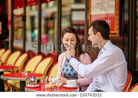 Happy couple drinking coffee or tea in a Parisian outdoor cafe