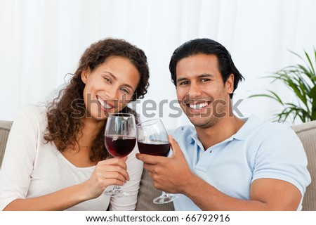 Happy couple drinking red wine sitting on the sofa at home - stock photo