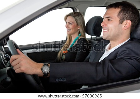 Happy couple driving a car - isolated over a white background