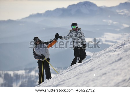 happy couple driving and relaxing with snowboard and ski at winter season on mountain - stock photo