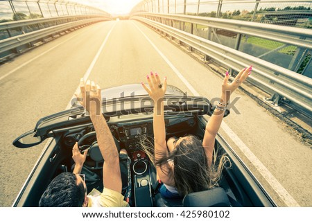 Happy couple driving on the road into the sunset in a sports car - stock photo