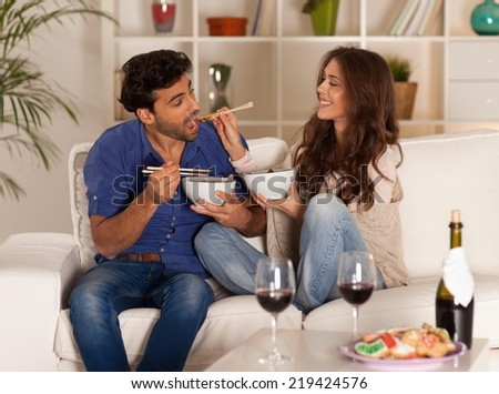 Happy couple eating chinese food and drinking wine at home. - stock photo