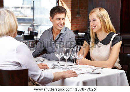 Happy couple eating with their parents-in-law in a restaurant