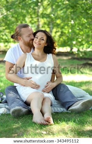 Happy couple embrace sitting on white blanket in the park