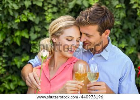 Happy couple embracing while toasting wineglasses at front yard - stock photo