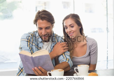 Happy couple enjoying a coffee reading a book at the coffee shop - stock photo