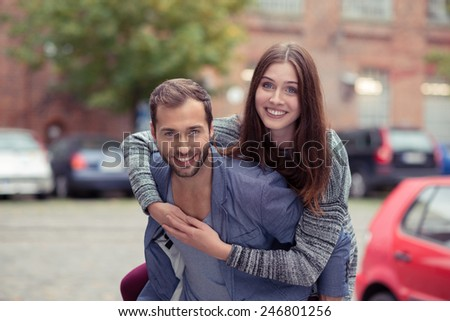 Happy couple enjoying a fun piggy back ride in an urban street looking at the camera with carefree friendly smiles - stock photo