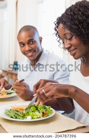 Happy couple enjoying a healthy meal together at home in the kitchen - stock photo