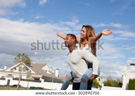 Happy couple enjoying flying on the street, female on man's back - stock photo