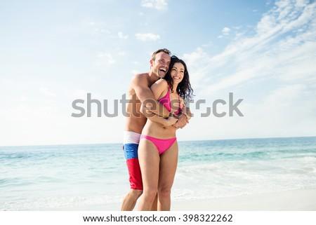 Happy couple enjoying on the beach on a sunny day - stock photo