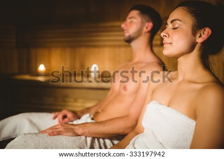 Happy couple enjoying the sauna together at the spa - stock photo