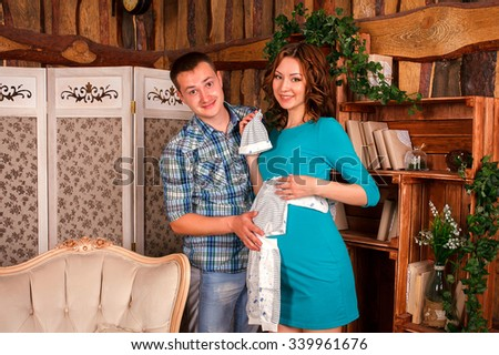 Happy Couple Expecting Baby. Beautiful Young Pregnant Woman and Her Husband Together Caressing Her Pregnant Belly at Home . Mom and Dad
