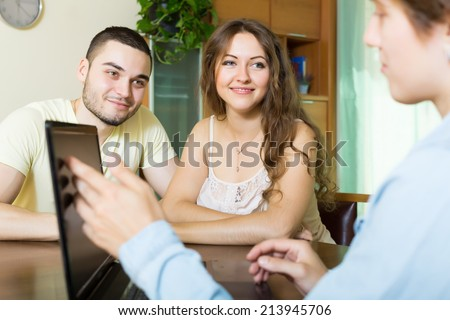 happy couple filling questionnaire for employee with laptop  - stock photo