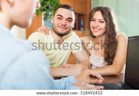 Happy couple filling questionnaire for employee with laptop of the bank at table