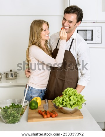 Happy couple fooling around while preparing healthy dinner - stock photo