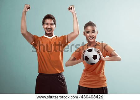 Happy couple football fan holding ball and cheering their team - stock photo