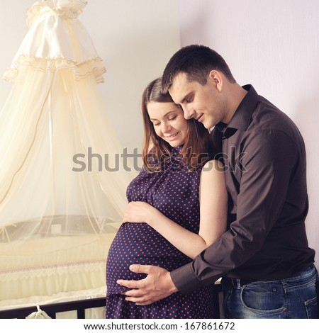 Happy couple future parents standing near a cot and looking on a tummy. - stock photo