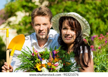 Happy couple gardening in summer with tools; she is wearing a hat