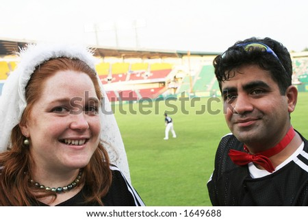 Happy couple get married at baseball stadium - intercultural marriage - stock photo