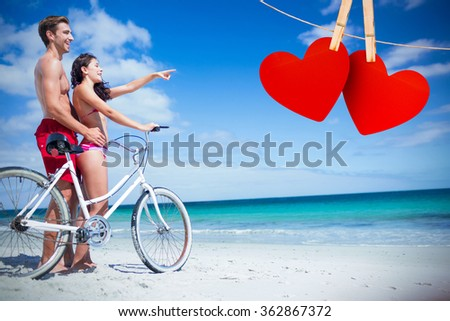 Happy couple going on a bike ride against hearts hanging on line - stock photo
