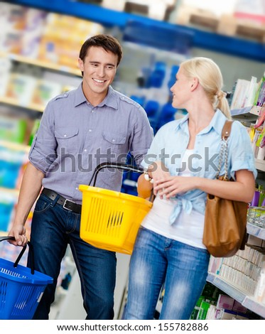 Happy couple handing carts in the shop. Concept of consumerism and retail - stock photo