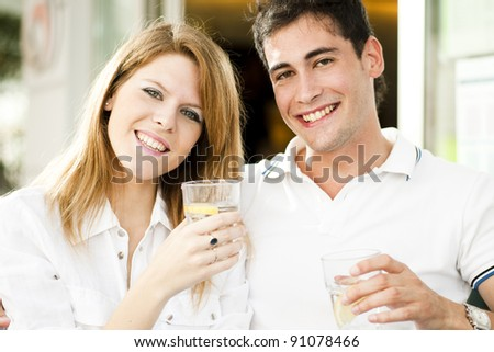 Happy couple having a drink and looking at camera - stock photo