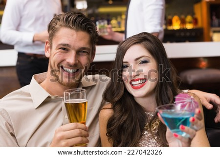 Happy couple having a drink together at the bar - stock photo