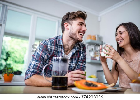 Happy couple having breakfast together at home - stock photo
