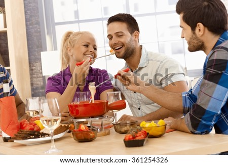 Happy couple having cheese fondue with friends, smiling. - stock photo