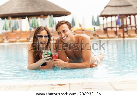 Happy couple having cocktails in the pool  - stock photo