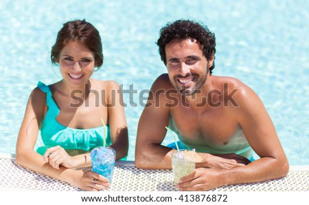 Happy couple having cocktails in the pool