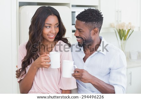 Happy couple having coffee together at home in the kitchen - stock photo