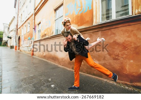 happy couple having fun in the rainy day in a orange background - stock photo