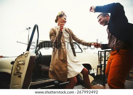 happy couple having fun near retro car - stock photo