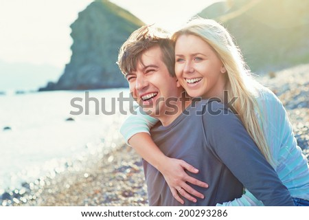 Happy Couple having fun on the Beach. - stock photo