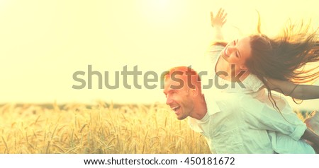 Happy Couple Having Fun Outdoors on wheat field over sunset. Laughing Joyful Family together. Freedom Concept. Piggyback