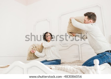 Happy Couple Having Pillow Fight in White Hotel Room