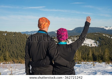 Happy couple hikers hugging  during winter travel in the Carpathian mountains. Back view. Sunny winter day in mountains. - stock photo