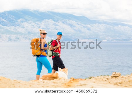 Happy couple hikers trekking with akita dog in summer mountains at seaside. Young woman and man walking on rocky mountain trail path looking at beautiful inspirational landscape view. - stock photo