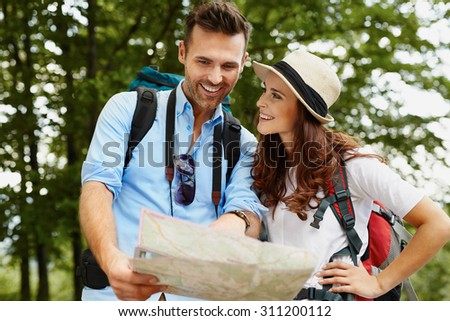 Happy couple hiking and reading map - stock photo