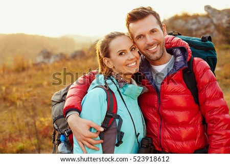 Happy couple hiking during autumn, fall with backpacks