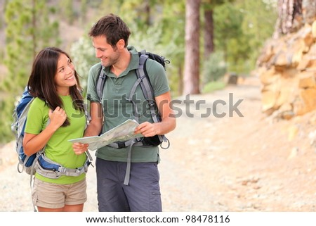 Happy couple hiking looking at map. Young interracial couple hikers smiling happy walking in forest during spring or summer. Asian woman, Caucasian man. - stock photo